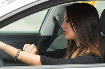 girl driving a car while looking at the time